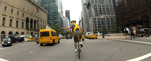 A cyclist scanning and signaling in traffic