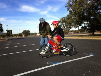 Pedaling and balancing, with instructor's hand on the bars for comfort